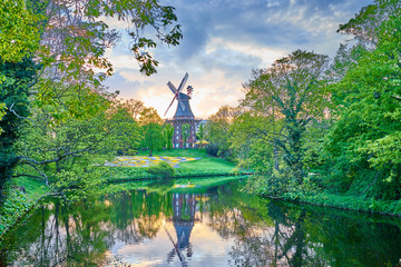 "Popular city park ""Wallanlagen"" with ""Am Wall Windmill"" at sunset in Bremen, Germany"