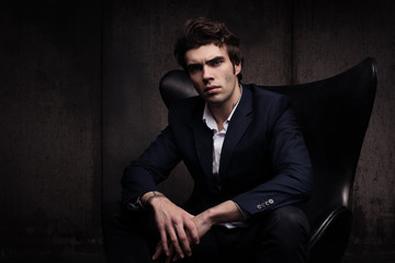 Portrait of a beautiful young man sitting in a chair. Stylish in appearance