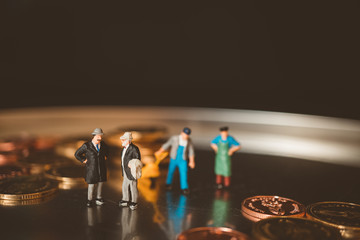 Miniature people, couple boss talking with worker lifting stack coins background using as business and financial concept