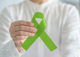 Lymphoma Cancer and mental health awareness Lime Green ribbon symbolic bow for raising support and helping patient living with illness