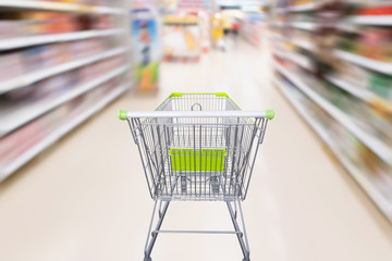 shopping cart with abstract motion blur supermarket discount store aisle and product shelves interior defocused background