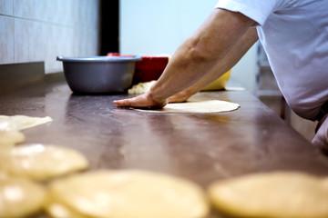 Man baker working in bakery shop