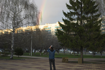 A man takes pictures of a rainbow on the phone.