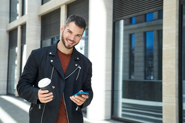 Portrait of handsome man with beard with cheerful positive emotions walking down the street on Sunny day with Cup of coffee