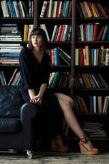 Brunette in black dress on background of books