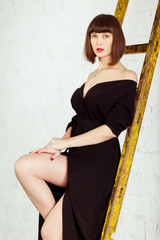 Photo of young brunette in black dress near stairs against white brick wall
