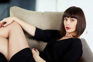 Photo of young brunette sitting on chair near window with blinds