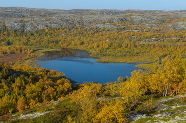Top view of the lake and hills with forest in autumn.