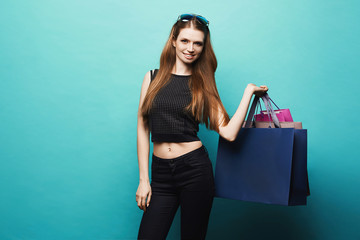 Sexy and beautiful model girl with perfect body and sunglasses on her head in stylish black t-shirt and in black jeans posing with shopping bags in her hand at blue background