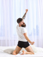 Guy stretching arms, full of energy in morning, rear view. Macho in underpants stretching, looking back and yawning. Man in shirt sits on bed, white curtains on background. Perfect morning concept.