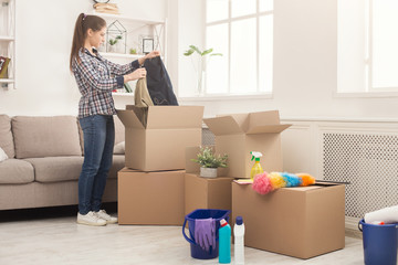 Young woman unpacking boxes after moving