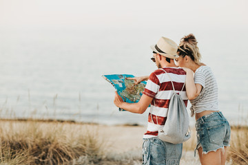 Young couple at the beach using map