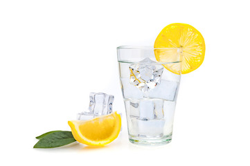 Water, lemon and ice cubes in a glass. Lemon slices next to a glass. Isolated.