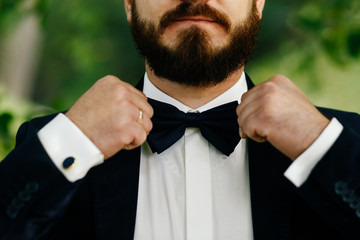 the bridegroom spits a black bow-tie. man with two hands touches a bow-tie