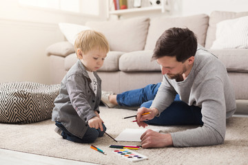 Father drawing with his little son