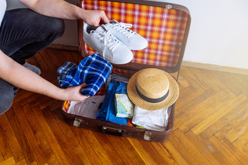 hands put sneakers to valise. packing for trip. travel concept