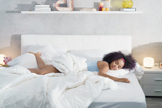 Black Woman Sleeping Alone in Large Bed