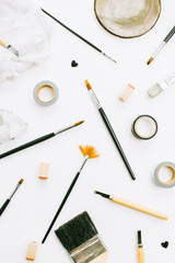 Artist workspace with paint brushes and tools on white background. Creative art concept. Flat lay, top view.