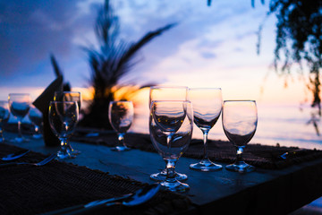 Glasses on table in tropical restaurant at sunset or sunrise