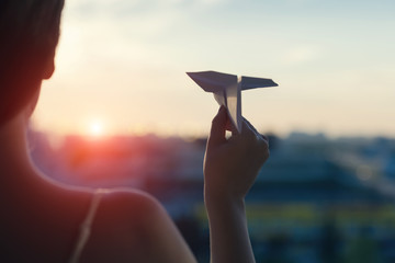 A girl is launching a paper airplane from a window at sunset.