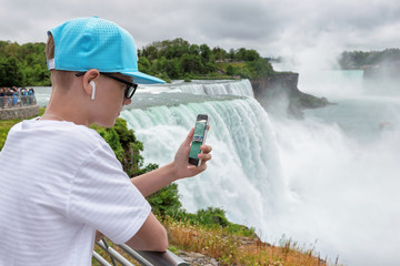 Teenager with spectacles takes a picture, video of the Niagara falls on a smartphone. Niagara Falls, USA.