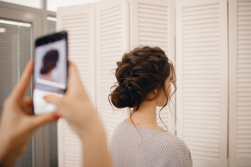 Hairdresser takes pictures of woman phone with finished hairstyle high beam on light background