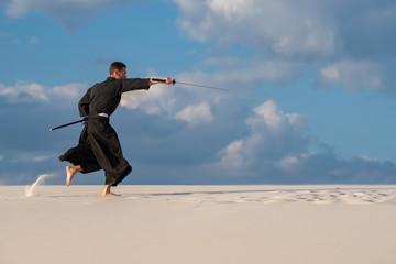 Resolute man practicing Japanese martial arts in desert