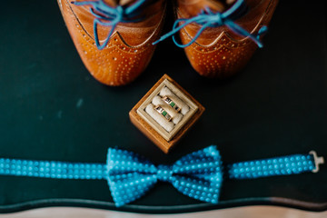Brown leather men's shoes with belt, bow-tie. Set groom accessories. Soft focus. Wedding rings in wooden decorated box. Coffee pot.