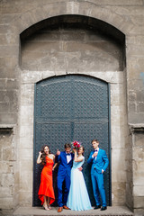 Full length portrait of newlywed couple dancing and having fun with bridesmaids and groomsmen in the old city center. Bride and groom with friends posing near old door and wall