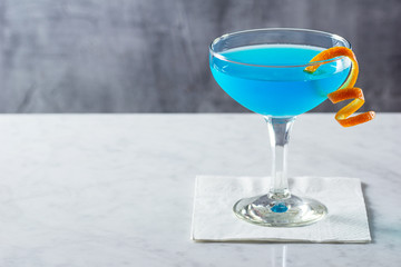 Chilled Blue Lagoon or Blue Hawaii Cocktail with Orange Twist in Glass on Marble Bar