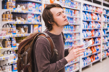 Young man is thinking about shopping with a tablet selects household chemicals in a supermarket
