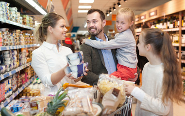 Family couple with their children are choosing meal for home