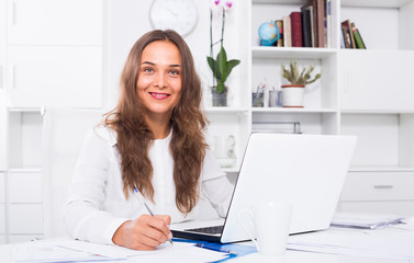 portrait of female business employee writing and working with laptop at office
