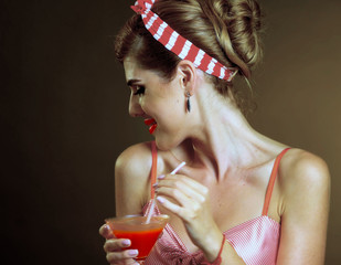 Pin up girl drink bloody Mary cocktail. Pin-up retro female style. Girl wearing red dress seduces men. How to arrange perfect party. Black white photo with accent. Girl is flirting in bar.