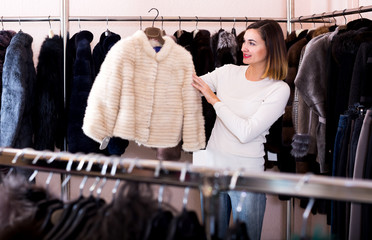 Female customer examining white mink jacket