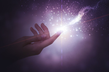 A hand giving the flow of energy. Magic, fantasy. Glowing particles