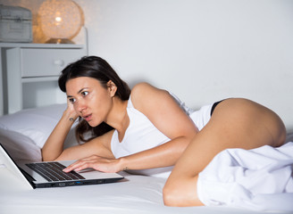Young sexy girl relaxing  with notebook on white sheet in bed