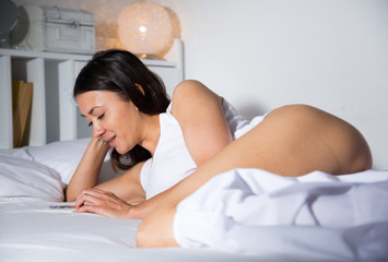 Young sexy girl lying  and using smartphone on white sheet in bed