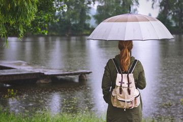 woman with umbrella and backpack standing in  rain at lake