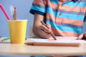 Child drawing with pencils at a table. Close view.