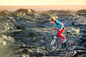 Young tourist cycling on lava field on Hawaii. Female hiker heading to lava viewing area at Kalapana on her bike. Tourist on hike near Kilauea volcano around Hawaii volcanoes national park, USA.