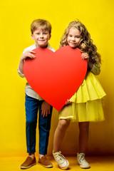 children holding big heart