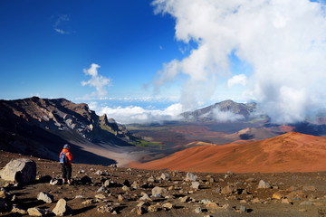 Tourist hiking in Haleakala volcano crater on the Sliding Sands trail. Beautiful view of the crater floor and the cinder cones below. Maui, Hawaii