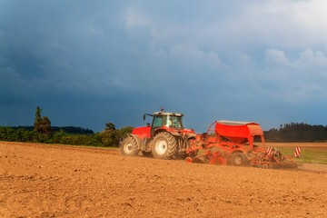 Red tractor in a dry field. Summer day at the farm in the Czech Republic. Agricultural work.