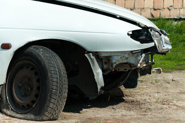 Crashed car with flat tire and demolished front end damaged in accident