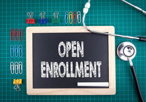 Open Enrollment concept. Medical and health background. Work desk with stationery and stethoscope.