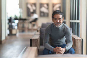 Portrait of happy mature man with white stylish short beard looking at camera. Casual lifestyle of retired hispanic people or adult asian man smile with confident sitting at modern coffee shop cafe.