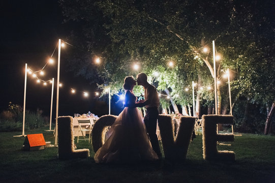 Beautiful newlyweds kiss tenderly at a wedding party with lamps. Stylish wedding ceremony. Love in the frame. Designer letters.