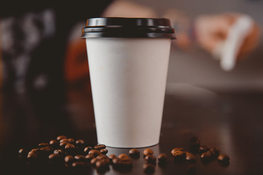 White paper cups of coffee with black caps presented in front grains lie on table. Food delivery concept