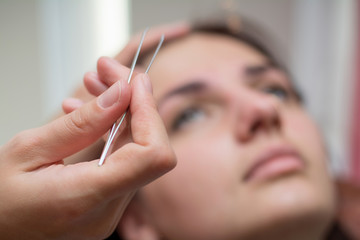 Beautiful young woman gets eyebrow correction procedure. Young woman painting her eyebrows in beauty saloon. close-up of a young woman plucking eyebrows with tweezers